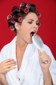 Woman with hair rollers singing into brush — Stock Photo