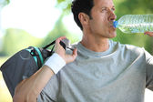 Athletic mature man drinking water from a bottle — Stock fotografie