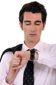 Businessman with coat over shoulder consulting his watch — Stock Photo