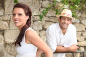 Couple standing by a stone wall — Stock Photo