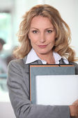 Businesswoman holding a file folder and a laptop — Stock Photo