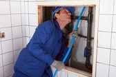 Atrás de uma parede, tubulação de alimentação azul de encanador — Foto Stock