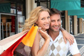 Portrait of a couple with shopping bags — Stock Photo