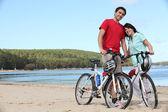 Ungt par med cyklar på en strand — Stockfoto