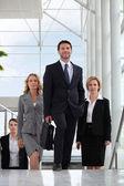 небольшая группа руководителей, ходить вверх лестнице в стеклянной крышей атриум — Стоковое фото