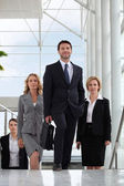 Small group of executives walking up stairs in a glass roofed atrium — Stockfoto