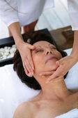 Woman having her face massaged — Stock Photo