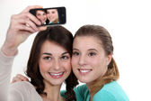 Girls taking picture with mobile phone — Stock Photo