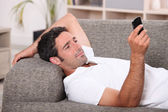 Amused man lying on the sofa sending a text message — Stock Photo
