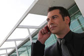 Businessman stood outside office telephoning — Stock Photo