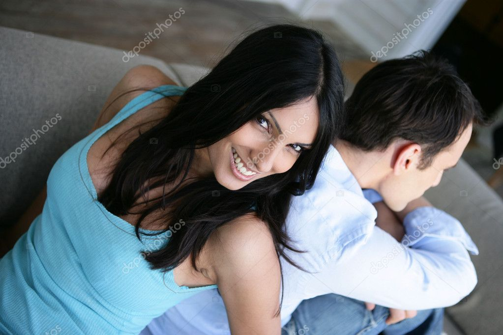Couple sat back to back on couch — Stock Photo #8408717
