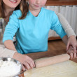 Mother and daughter rolling out pastry — Stock Photo