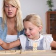 Young woman and her daughter playing dominoes — Stock Photo