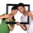 Couple holding empty art frame — Stock Photo