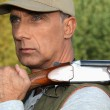 Stock Photo: Hunter with rifle outdoors