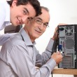 Grandson and grandfather connecting a computer — Stock Photo