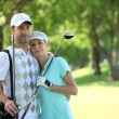 Stock Photo: Golfing couple hugging on course