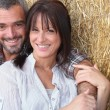Farming couple sitting in the hay — Stock Photo