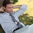 Young man relaxing in the grass with laptop — Stock Photo #8410732