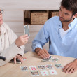 Young man playing cards with older woman — Stock Photo