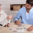 Foto de Stock  : Young man playing cards with older woman