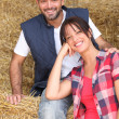 Farmer and wife sitting on hay — Stock Photo