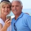 Mature couple taking a picture of themselves by the sea — Stock Photo #8411126