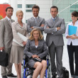 Woman in a wheelchair and team — Stock Photo