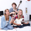 Stock Photo: Three teenage musicians sitting in bed room