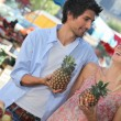 Young couple holding pineapples at a market stall — Stock Photo #8411630