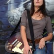 Royalty-Free Stock Photo: Cool female guitarist standing against graffiti