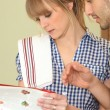 Couple looking for a recipe  in a cookbook — Stock Photo