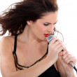 Young female singer with microphone — Stock Photo