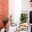 Women at restaurant with waiter — Stock Photo