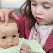 Little girl putting a plaster on her baby doll's forehead — Stock Photo