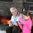 Stock Photo: Little girl playing card game with granddad