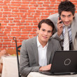 Businessmen smiling working on laptop — Stock Photo