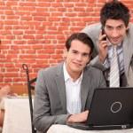 Businessmen smiling working on laptop — Stock Photo