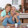 Middle-aged couple having breakfast together in kitchen — Fotografia Stock  #8419670