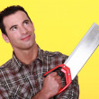 Smiling man with a tenon saw - Stock Photo