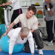Stock Photo: Older working out with a personal trainer in a gym