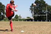 Gracz rugby, kopiąc piłkę — Zdjęcie stockowe