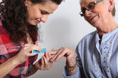 Elderly woman having her nails filed — Stock Photo