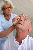 Woman helping husband with contact lenses — Stock Photo