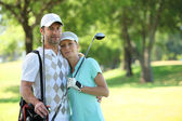 Golfing couple hugging on a course — Stock Photo