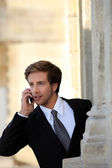 Young businessman on the phone by a stone building — Stock Photo