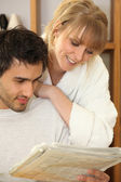 Young couple looking at a morning paper — Stock Photo