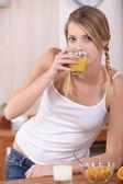 Ung kvinna äter frukost — Stockfoto