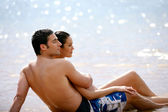 Couple sat together on a beach — Stockfoto