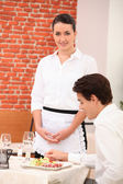 Waitress awaiting table — Stock Photo